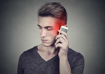 Man on the cellphone with headache. Upset unhappy guy talking on a phone isolated on gray wall background. Negative human emotion face expression feeling reaction.