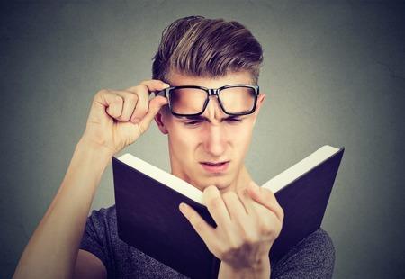 Człowiek z okularami cierpiących na zmęczenie oczu czytając książkę o problemy ze wzrokiem