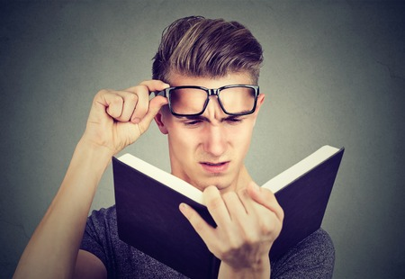 Man with glasses suffering from eyestrain reading a book having vision problems