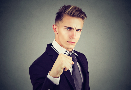 Angry business man with closed fist looking at camera on gray background Stock Photo