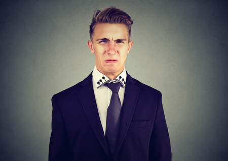 Portrait of a disgusted young business man isolated on gray wall background  Stok Fotoğraf