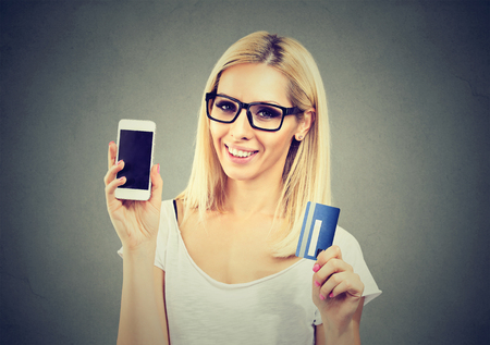 Cheerful young woman with mobile phone and credit card over gray background