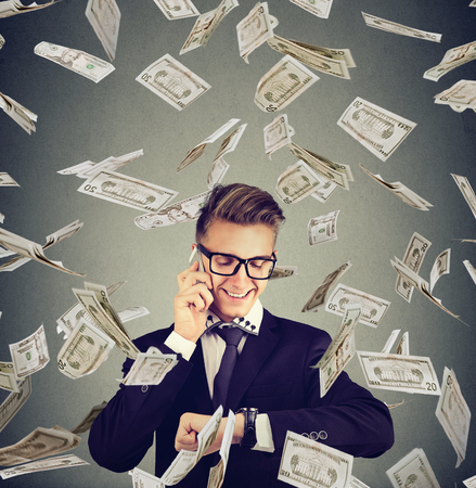 Business management. Busy happy businessman looking at wrist watch, talking on mobile phone under cash rain. Time is money concept