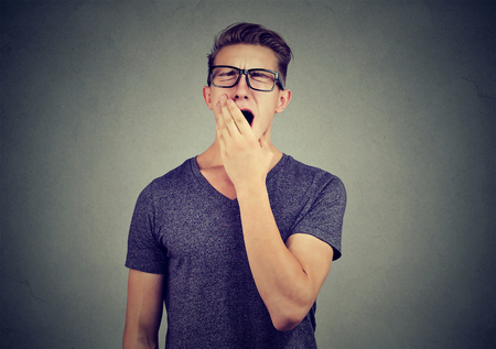 Young man yawning with hand over his mouth  Stock Photo