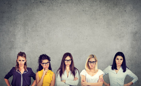 Group of angry negative women looking at camera while standing against concrete wall background