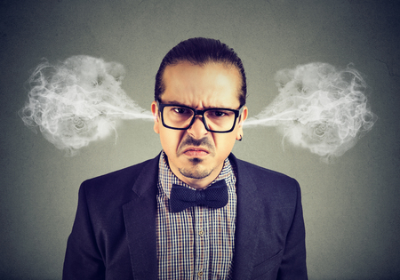 Angry business man, blowing steam coming out of ears, about to have nervous breakdown isolated on gray background. Negative emotions facial expression feelings
