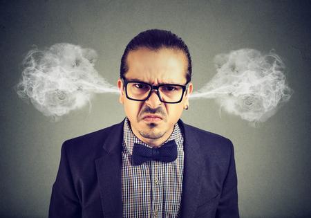 Boze bedrijfsmens, blazende stoom die uit oren komen, ongeveer om zenuwinzinking te hebben die op grijze achtergrond wordt geïsoleerd. Negatieve emoties gezichtsuitdrukking gevoelens