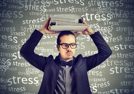 Stressed doomed business man standing with heavy folders on his head isolated on gray background Stock Photo