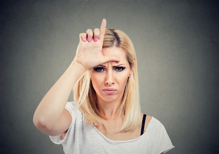 Closeup portrait unhappy woman giving loser sign on forehead, looking at you with anger and hatred on face isolated on gray background.