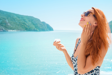 woman applying sunscreen sunblock lotion by seaside smiling happy outdoors Zdjęcie Seryjne - 91446513