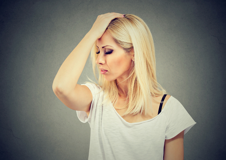 Young woman holding hand on head looking forgetfully and trying to remember something.