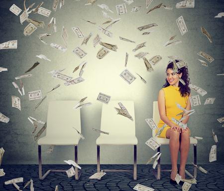 Cheerful model sitting on chair with dollar bills flying around under money rain
