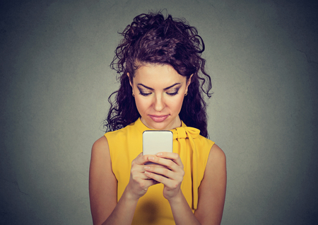 Young beautiful woman immersed into using smartphone looking focused on screen. Stock Photo