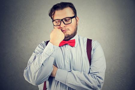 Jonge man met overgewicht poseren in strikje en bril op zoek verdrietig.