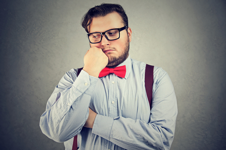 Young man with overweight posing in bow-tie and eyeglasses looking sad.