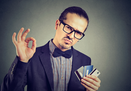 Young elegant man in eyeglasses showing OK gesture posing with few credit cards.