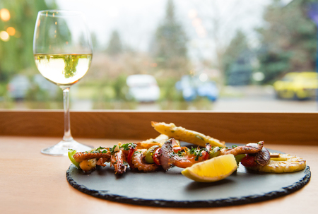 Delicious seafood assortment with shrimp and octopus served on slate plate with glass of white wine.  Stock Photo