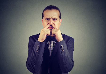 Elegant man pinching his nose looking discontent with terrible stench.