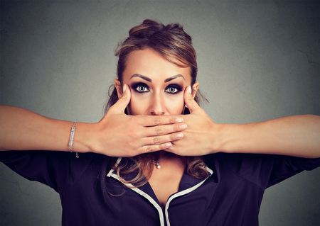 Young woman covering mouth with hands unable to express real feelings and looking at camera.