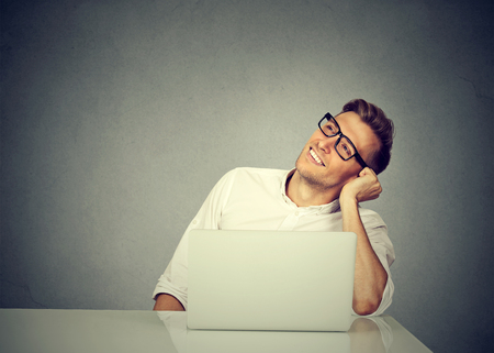 Young man at workplace with laptop leaning on table and daydreaming happily on gray background.