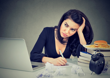 Young woman overwhelmed with work looking stressed while sitting at table in office.  Stock Photo