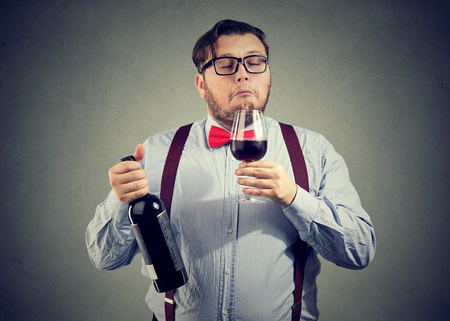 Concentrated man holding bottle of wine and smelling beverage with eyes closed on gray backdrop.  Stok Fotoğraf