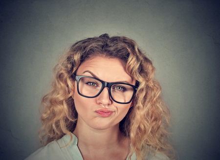 Young model in eyeglasses having doubts and looking bitchy at camera.