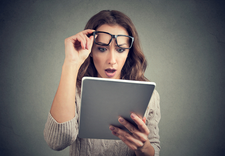 Young girl in eyeglasses watching tablet with shock having bad news and posing on gray.