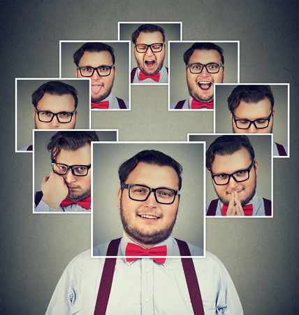 Young man looking expressive having changes of mood while posing on gray.  Stock Photo