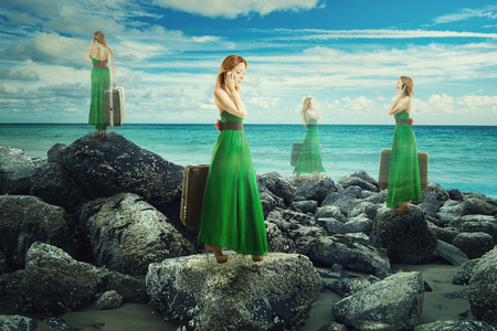 Translucent woman in green dress with suitcase walking in infinite time on rocky shoreline.