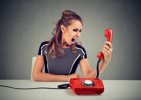 Young formal woman holding red phone handset and shouting madly.