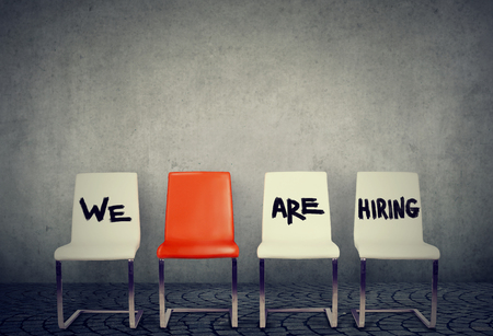Row of chairs saying We are hiring offering vacant places.  Stockfoto