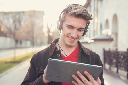 Young casual man in earphones chilling and using tablet on urban background.