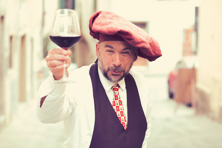 Mature eccentric man offering glass of self made wine looking excitedly at camera.  版權商用圖片