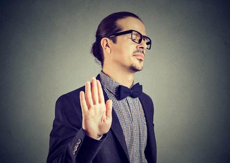 Joven elegante en anteojos parando con la mano mientras se ve molesto e insultado. Foto de archivo