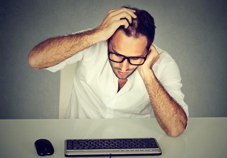 Formal man in eyeglasses scratching head trying to remember password looking at keyboard. Reklamní fotografie