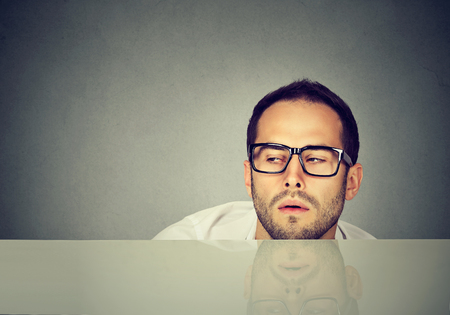 Young casual man in eyeglasses looking exhausted while working while day long.