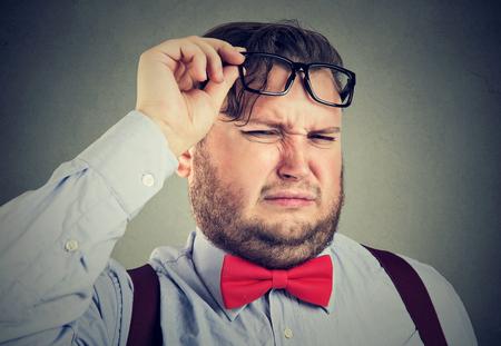 Man wearing eyeglasses and having expression of aversion looking at camera.