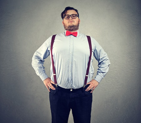 Man with overweight posing in red bowtie with great feeling of self importance looking at camera. Reklamní fotografie