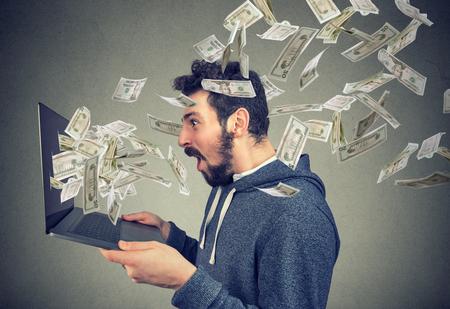 Side view of man holding laptop and winning plenty of money in social media.  Zdjęcie Seryjne