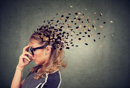 Geheugenverlies door dementie of hersenschade. Zijprofiel van een vrouw die delen van het hoofd verliest als symbool van verminderde geestesfunctie.