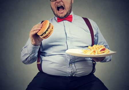 big man in formal clothes sitting and consuming plate with fast food on gray.