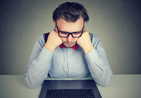 Bored business man with no motivation sitting at desk with laptop computer