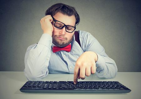 Młody otyły mężczyzna siedzi w miejscu pracy i ociąga się, będąc leniwy i rozkojarzony. Zdjęcie Seryjne