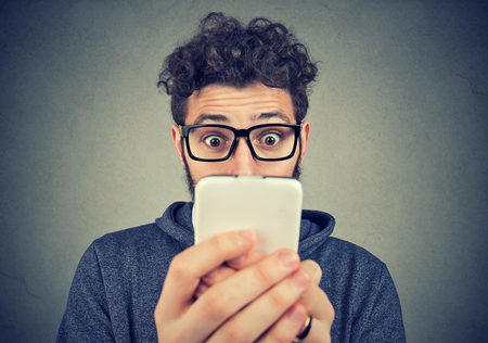 Young bearded man in glasses using phone with expression of great astonishment.