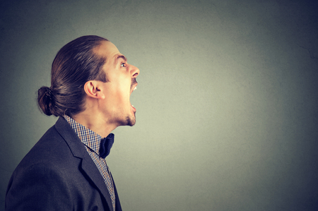 Side view of angry business man yelling in madness looking away.