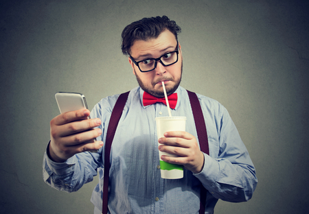 Young chubby man addicted to social media and network using phone and drinking sweet soda.