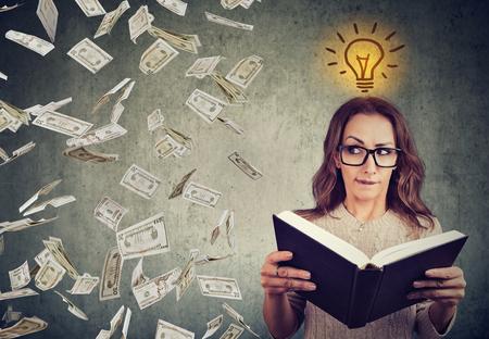 Woman student reading a book has a bright idea how to earn money  Фото со стока