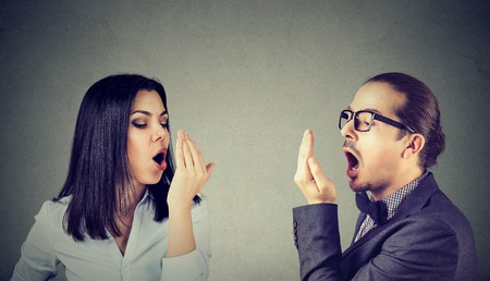 Young couple woman and man checking their breath with hand gesture  스톡 콘텐츠