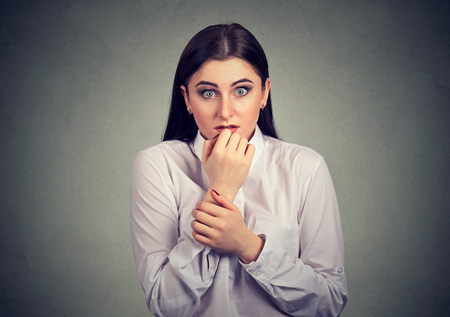 Young anxious woman biting nails and looking at camera with feeling of panic.